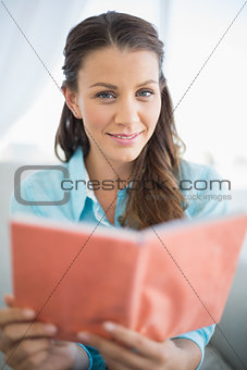 Peaceful woman sitting on sofa reading book