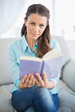Happy woman sitting on couch holding book