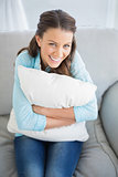 Happy woman holding pillow sitting on couch