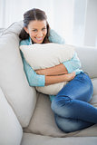 Cheerful woman holding pillow sitting on couch
