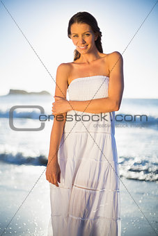 Calm woman in white summer dress posing