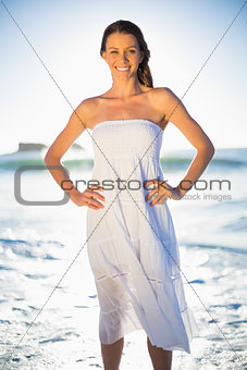 Beautiful brunette in white summer dress posing