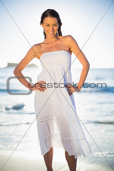 Smiling brunette in white summer dress posing