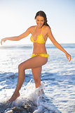 Happy gorgeous woman in yellow bikini having fun in the sea
