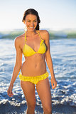 Cheerful gorgeous woman in yellow bikini bathing in the sea