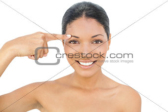Smiling black haired model pointing at her eyebrow
