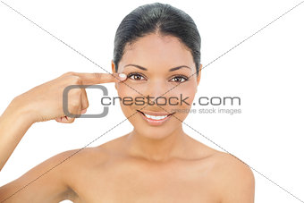 Smiling black haired model pointing at her eye