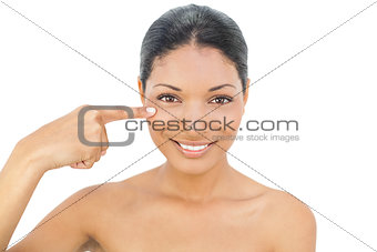 Cheerful black haired model pointing at her cheek