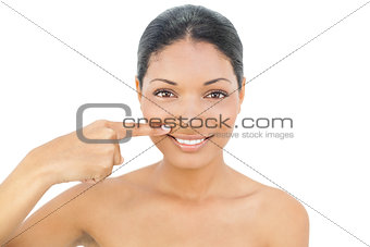 Smiling black haired model pointing above her lips