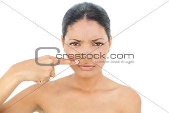 Frowning black haired model pointing above her lips