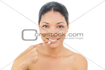 Smiling black haired model pointing at her bottom lip