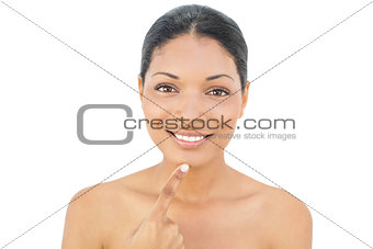 Smiling black haired model pointing at her chin