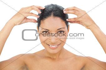Smiling black haired model massaging her head