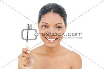 Smiling black haired model holding eyebrow brush