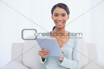 Smiling attractive woman using her digital tablet