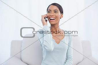 Smiling attractive woman on the phone sitting on cosy sofa