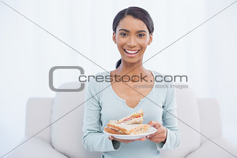 Smiling attractive woman sitting on cosy sofa holding sandwich