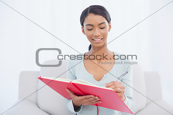 Smiling attractive woman sitting on cosy sofa writing