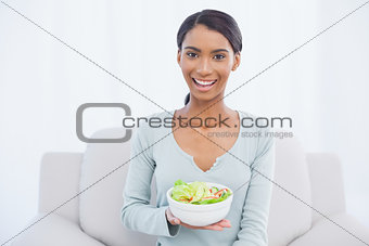Smiling attractive woman sitting on cosy sofa holding salad