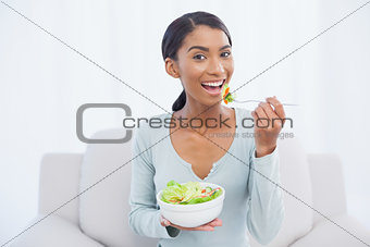 Smiling attractive woman sitting on cosy sofa eating salad