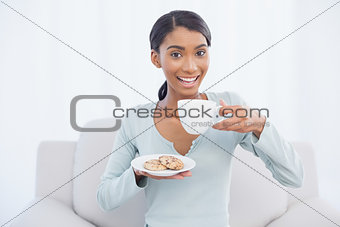Smiling attractive woman sitting on cosy sofa holding coffee and cookies