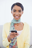 Smiling pretty woman sitting on sofa text messaging