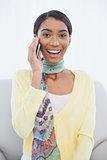 Smiling pretty woman sitting on sofa having a phone call