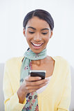 Smiling elegant woman sitting on sofa text messaging