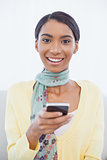 Cheerful elegant woman sitting on sofa text messaging