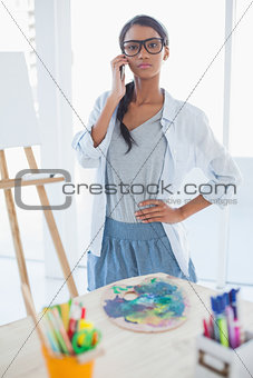Serious pretty artist having a phone call