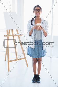 Smiling attractive artist holding cup of coffee