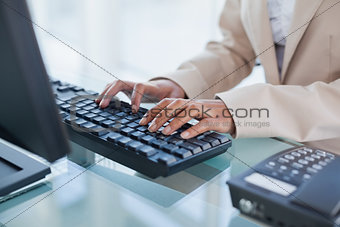 Close up on businesswoman typing on her keyboard