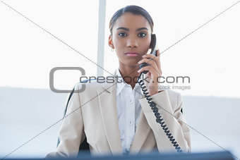 Stern elegant businesswoman on the phone