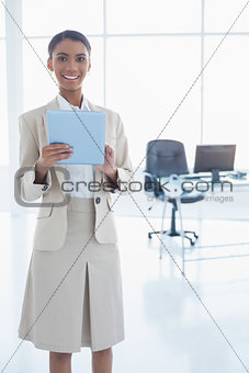 Smiling elegant businesswoman using her tablet