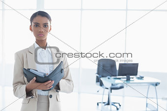 Stern elegant businesswoman holding her agenda