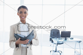 Smiling elegant businesswoman holding her agenda
