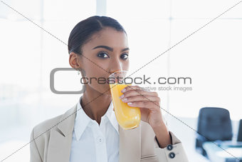 Smiling elegant businesswoman drinking orange juice