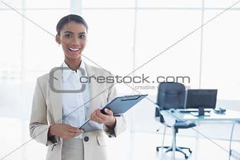 Smiling elegant businesswoman holding clipboard