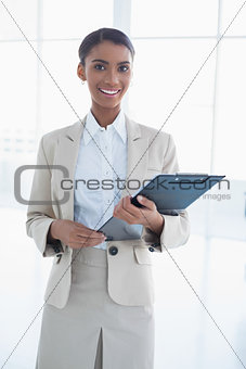 Cheerful elegant businesswoman holding clipboard