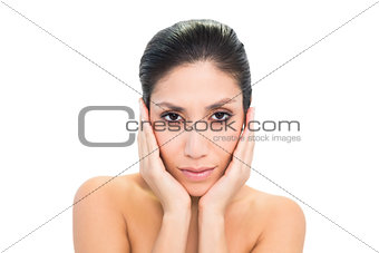 Peaceful brunette touching her face with both hands