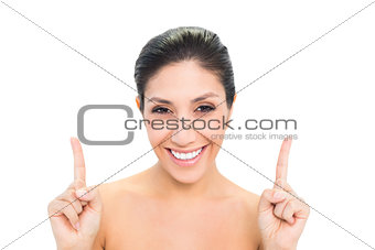 Smiling brunette pointing up with both hands