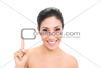 Smiling brunette pointing up with one hand