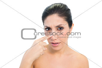 Worried brunette pointing to nose and looking at camera