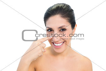 Smiling brunette pointing to nose and looking at camera