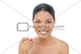 Smiling black haired model applying lip gloss
