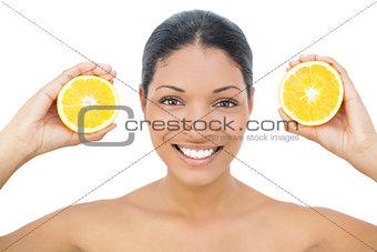 Smiling black haired model holding orange slices