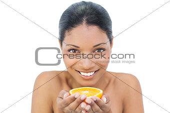 Smiling black haired model holding orange slice