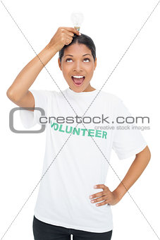 Happy model wearing volunteer tshirt holding light bulb above her head
