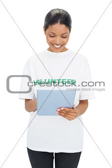 Smiling model wearing volunteer tshirt holding tablet