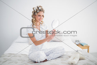 Gorgeous blonde looking at reflection on cosy bed
